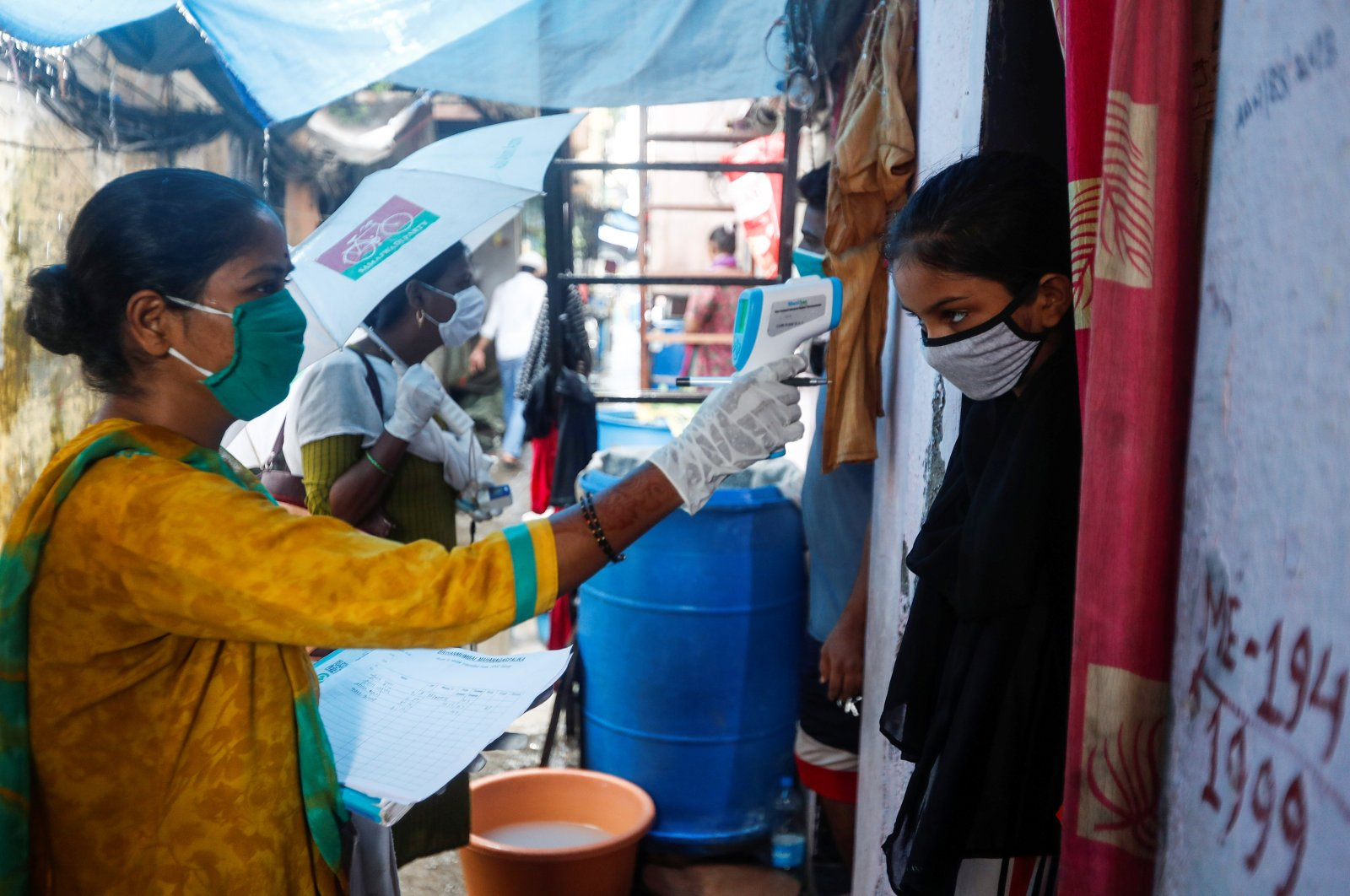 A community health volunteer checks the temperature of a girl during a checkup campaign at a slum in Mumbai, India, Aug. 17, 2020. (Reuters Photo)