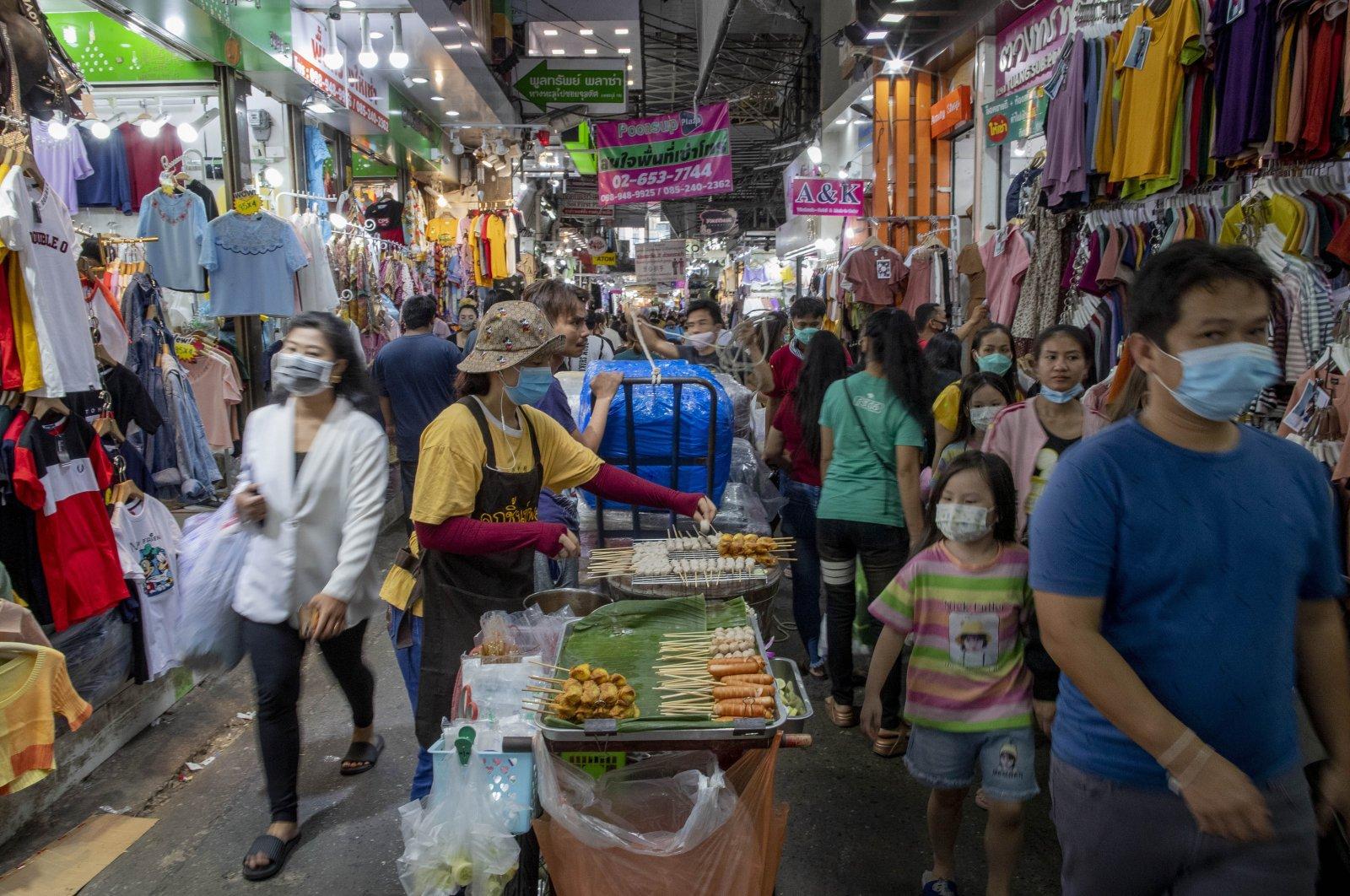 Shoppers walk through a clothing market in Bangkok, Thailand, Aug. 6, 2020.  (AP Photo)