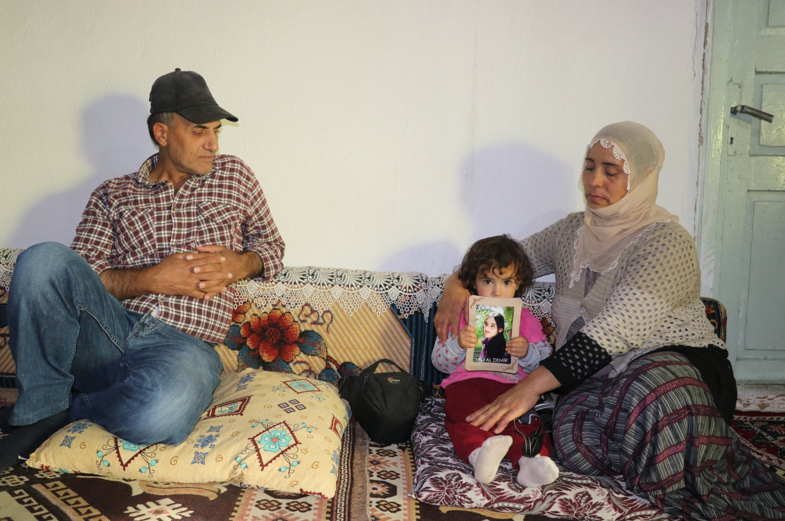Süheyla Demir and Mustafa Demir sit down in their house in Ağrı with their youngest daughter Asmin, who holds the picture of her kidnapped sister, Hayal, Aug.17, 2020. (AA Photo)