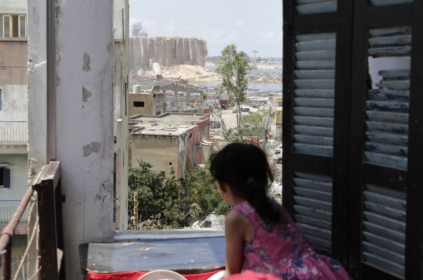 A girl stands at the window of her apartment overlooking the destroyed silo on at Beirut's port, Aug. 11, 2020. (AFP Photo)