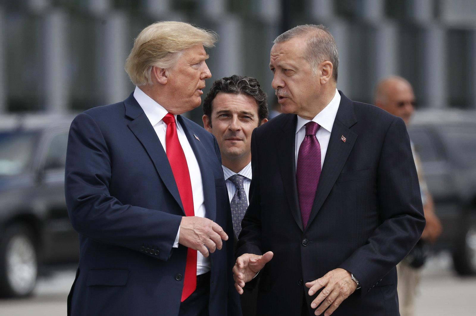 U.S. President Donald Trump (L) talks with President Recep Tayyip Erdoğan as they arrive together for a family photo at a summit of heads of state and government at NATO headquarters in Brussels, July 11, 2018. (AP Photo)