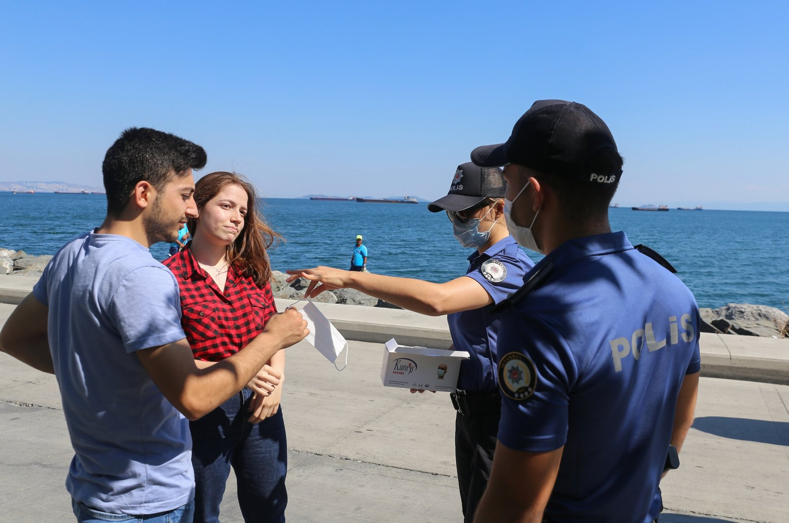 Police officers hand out masks to a couple walking on Bakırköy coastline without a mask, Istanbul, Turkey, Aug. 11, 2020. (AA Photo)