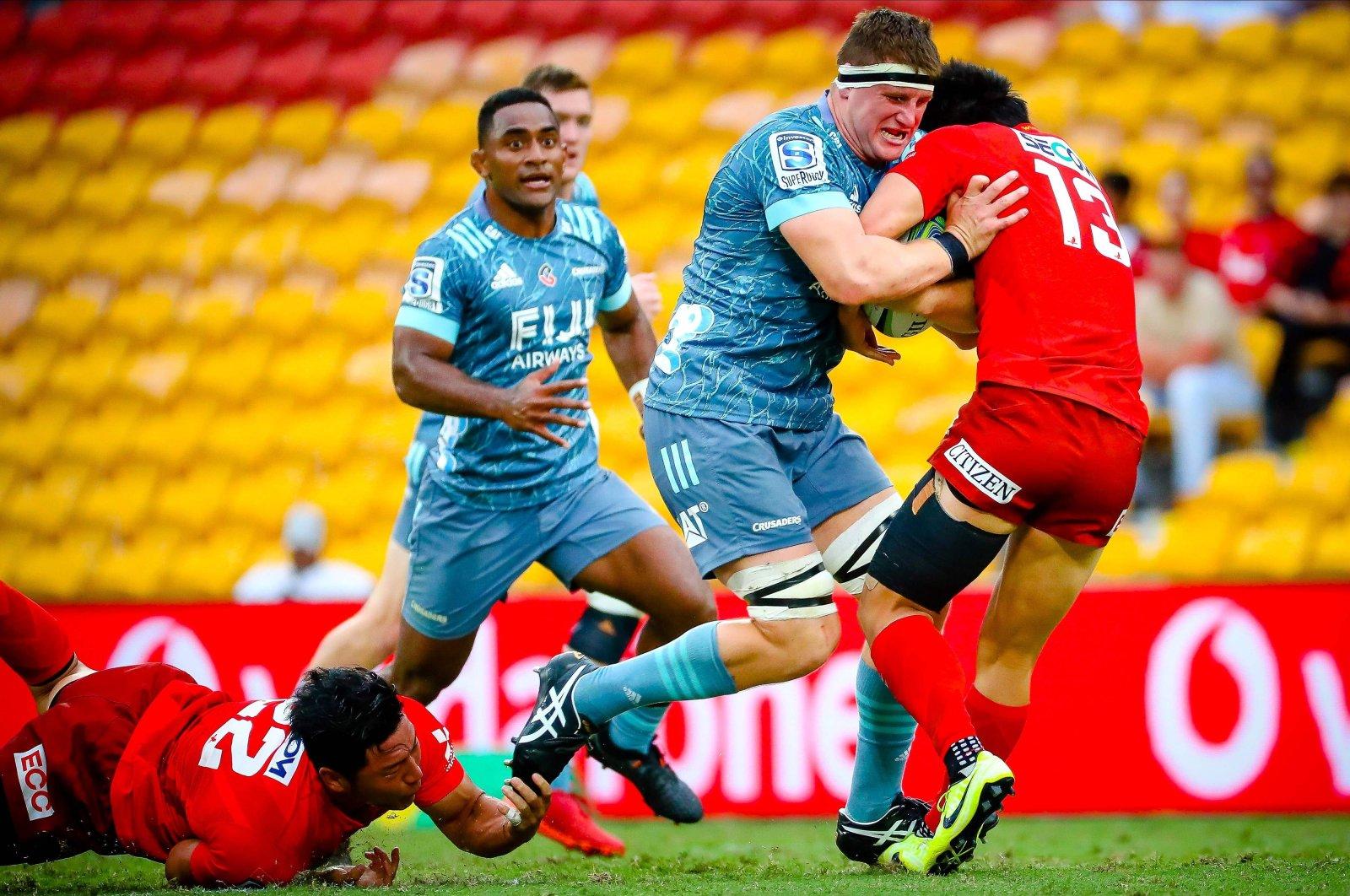 Crusaders' Tom Sanders is tackled by Sunwolves' Shogo Nakano (L) and Keisuke Moriya (R) during the Super Rugby match between Sunwolves and Crusaders, in Brisbane, Australia, March 14, 2020. (AFP Photo)