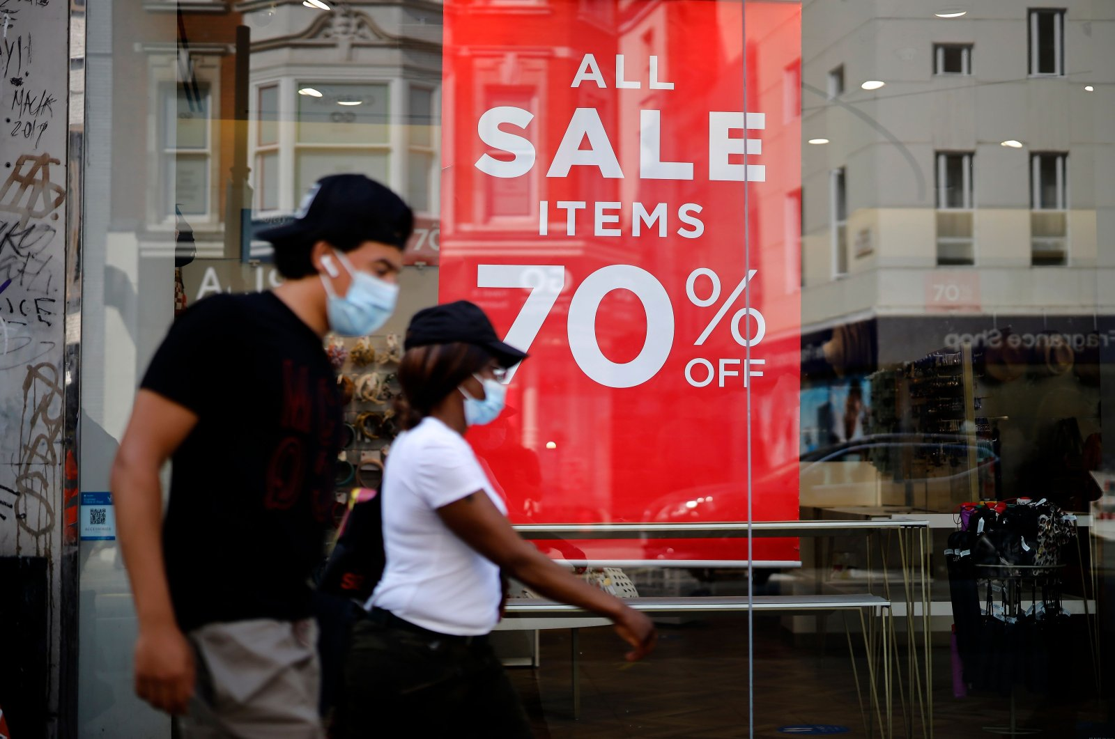 Shoppers wearing face coverings due to the COVID-19 pandemic walk past sales signs in a shop window in London, Aug. 12, 2020. (AFP Photo)