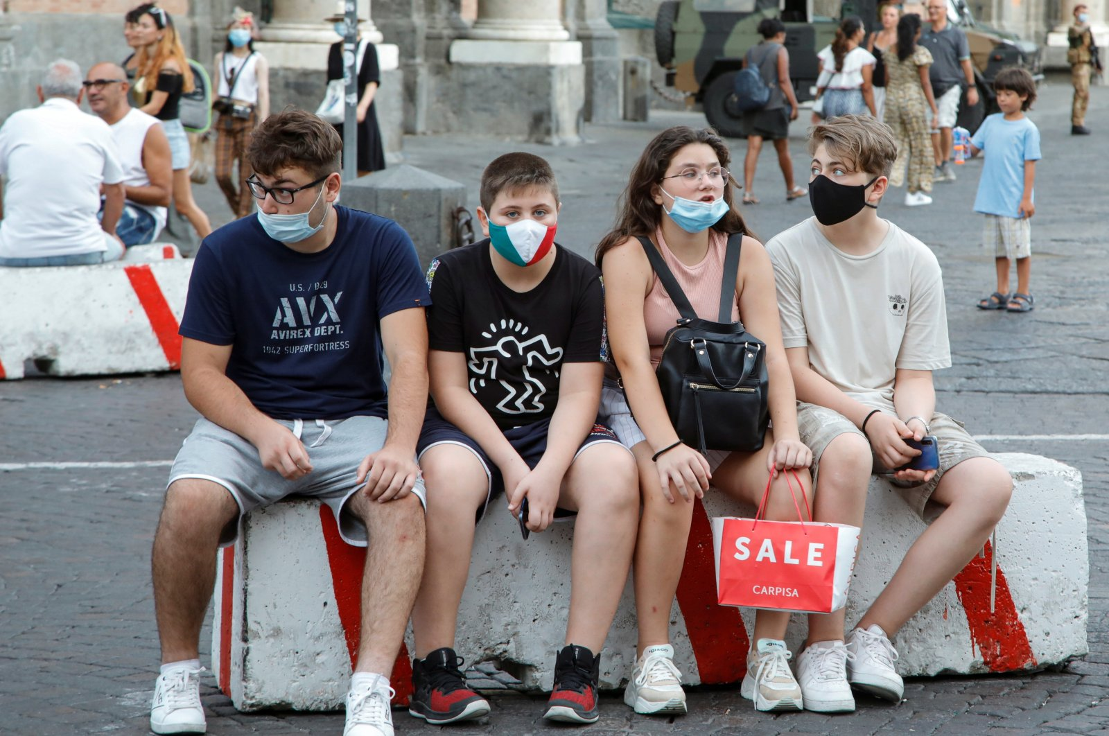 Young people wear masks as they sit on a car barrier following a government decree that face coverings must be worn between 6 p.m. and 6 a.m. in areas close to bars and pubs and where gatherings are more likely, Naples, Italy, Aug. 17, 2020. (Reuters Photo)