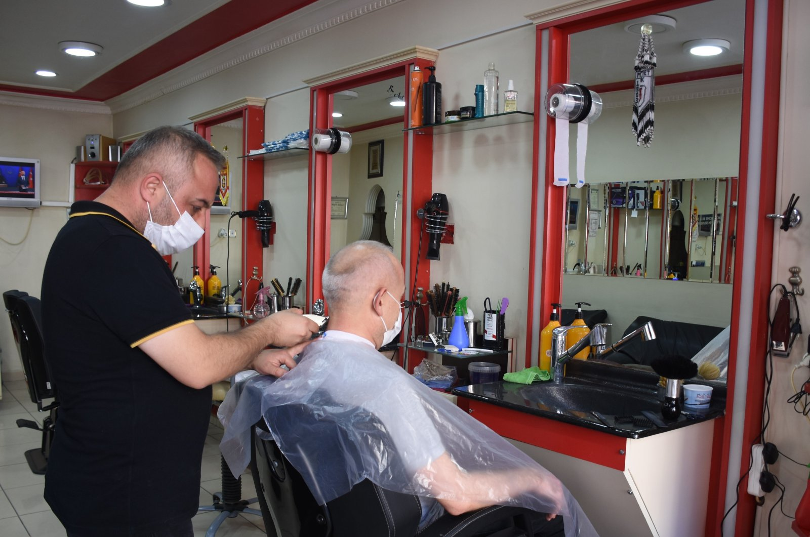 A barber cuts the hair of a customer in a barbershop certified as safe, in Kırıkkale, central Turkey, Aug. 17, 2020. (AA Photo)