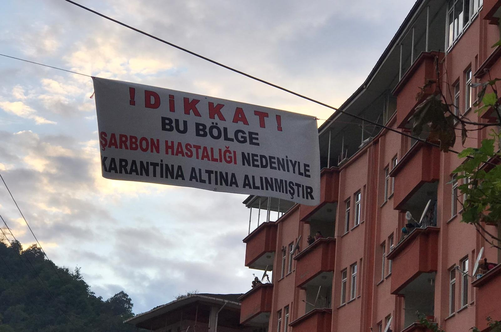 """A sign reading """"Attention! This place is quarantined due to anthrax"""" hangs between buildings in the Sürmene district in Trabzon, northern Turkey, Aug. 18, 2020. (DHA Photo)"""