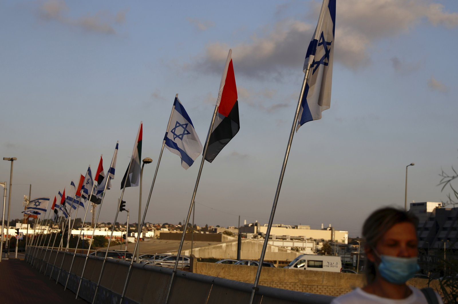 A woman wearing a face mask against the coronavirus walks past United Arab Emirates and Israeli flags at the Peace Bridge in Netanya, Israel, Sunday, Aug. 16, 2020. (AP Photo)