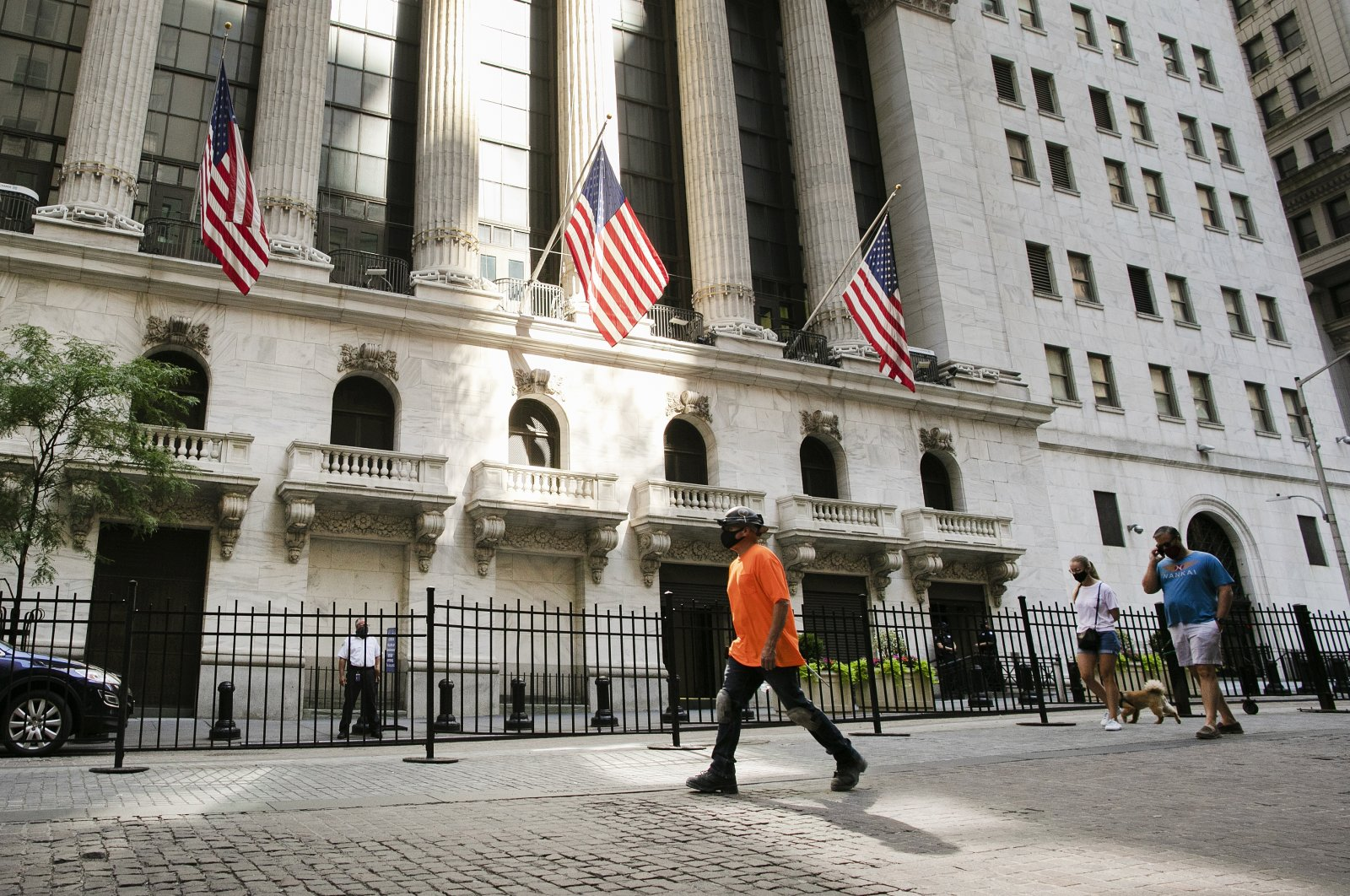 People walk by the New York Stock Exchange, New York City, U.S., July 21, 2020.