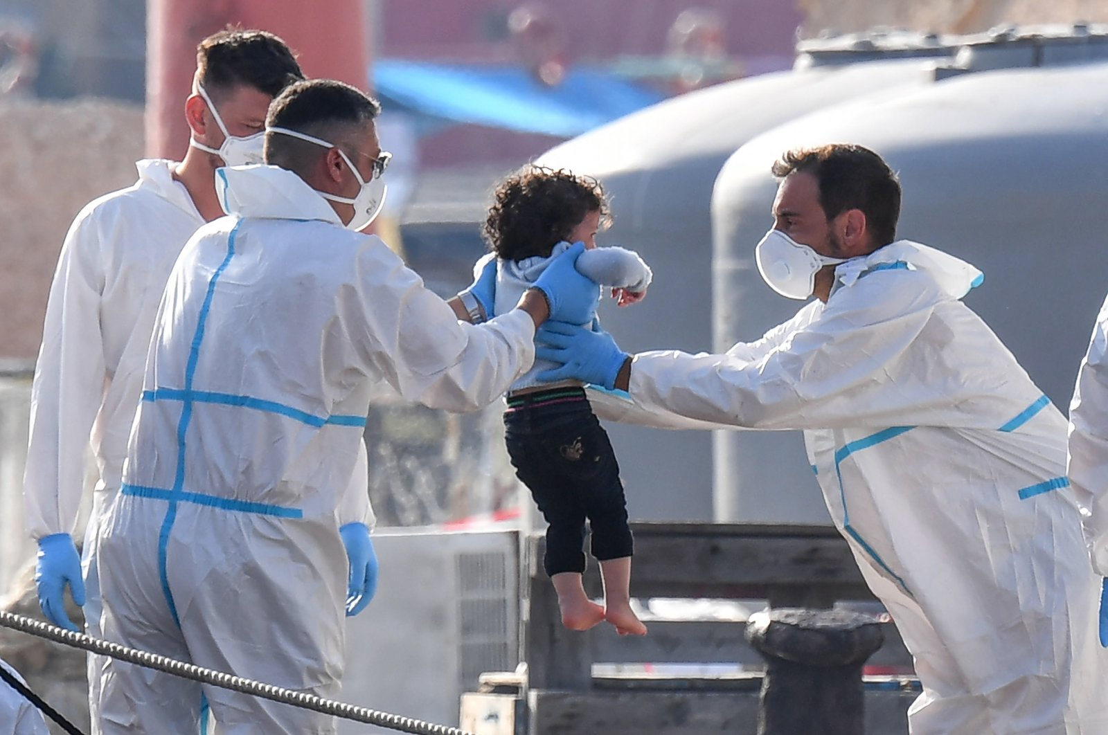 Italian immigration officers help a child disembark from a ship as a group of migrants arrives from North Africa on the island of Lampedusa, southern Italy, Aug. 3, 2020. (EPA Photo)