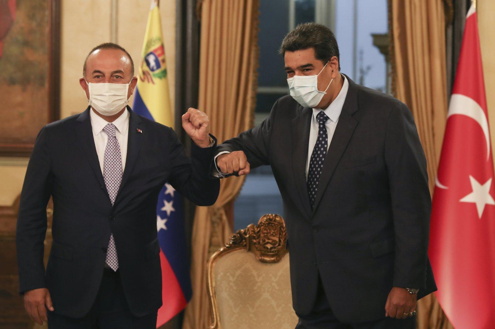 Foreign Minister Mevlüt Çavuşoğlu and Venezuela's President Nicolas Maduro touch elbows as they pose for photos before their talks, in Caracas, Venezuela, Aug. 18, 2020. (AP Photo)