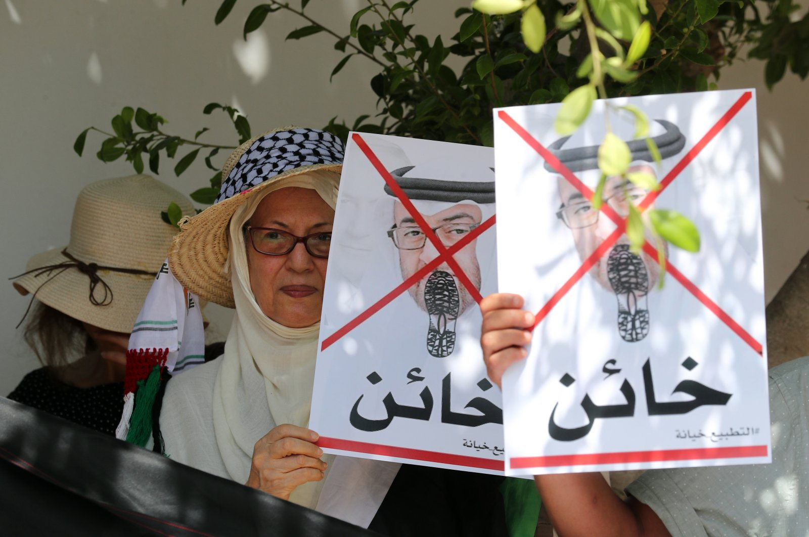 """Tunisian protesters hold crossed out portraits of Abu Dhabi Crown Prince Sheikh Mohammed bin Zayed Al Nahyan with the word """"traitor"""" written underneath it, during a protest against the leaders of the United Arab Emirates after forming diplomatic relations with Israel, in front of the UAE embassy in Tunis, Tunisia, Aug. 18, 2020. (EPA Photo)"""