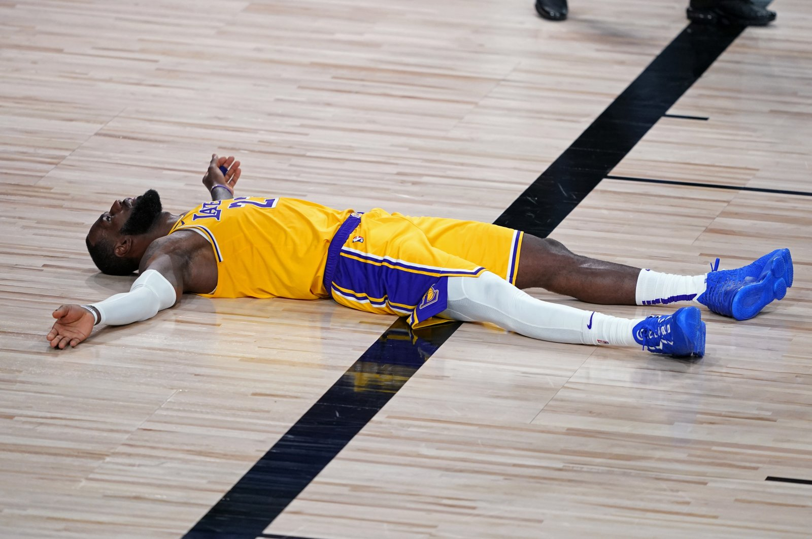 Los Angeles Lakers forward LeBron James (23) lies on the court after committing a foul during the second half of an NBA basketball game against the Portland Trail Blazers in Lake Buena Vista, Florida, U.S., Aug. 18, 2020. (AP Photo)