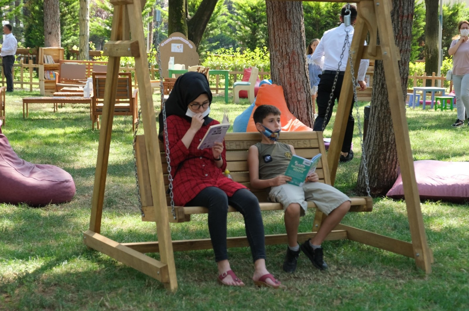 A girl and a boy sitting on a swing read books at the outdoor library, in Bursa, northwestern Turkey, Aug. 19, 2020. (AA Photo)