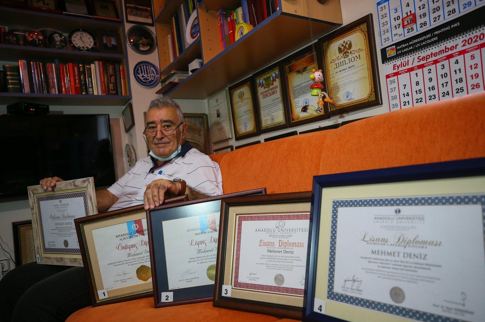 Mehmet Deniz shows his diplomas in his home, in Izmir, western Turkey, Aug. 19, 2020. (AA Photo)