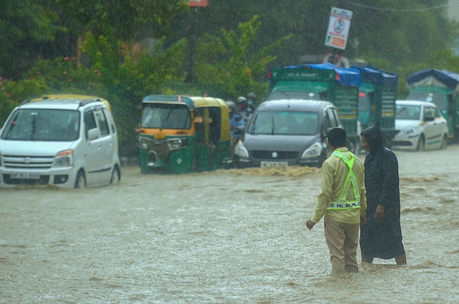 Commuters make their way as municipal workers stand along a waterlogged road following monsoon rainfalls, New Delhi, India, Aug. 19, 2020. (AFP Photo)