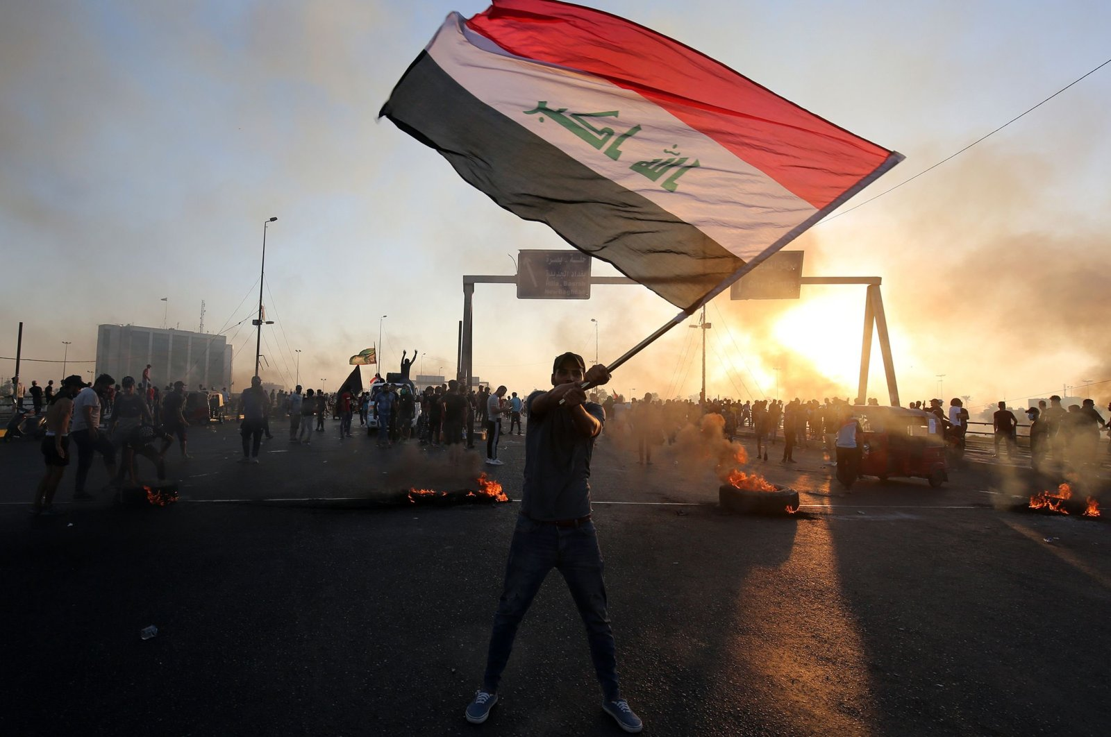 An Iraqi protester waves the national flag during a demonstration against state corruption, failing public services and unemployment in the Iraqi capital Baghdad, Oct. 5, 2019. (AFP Photo)