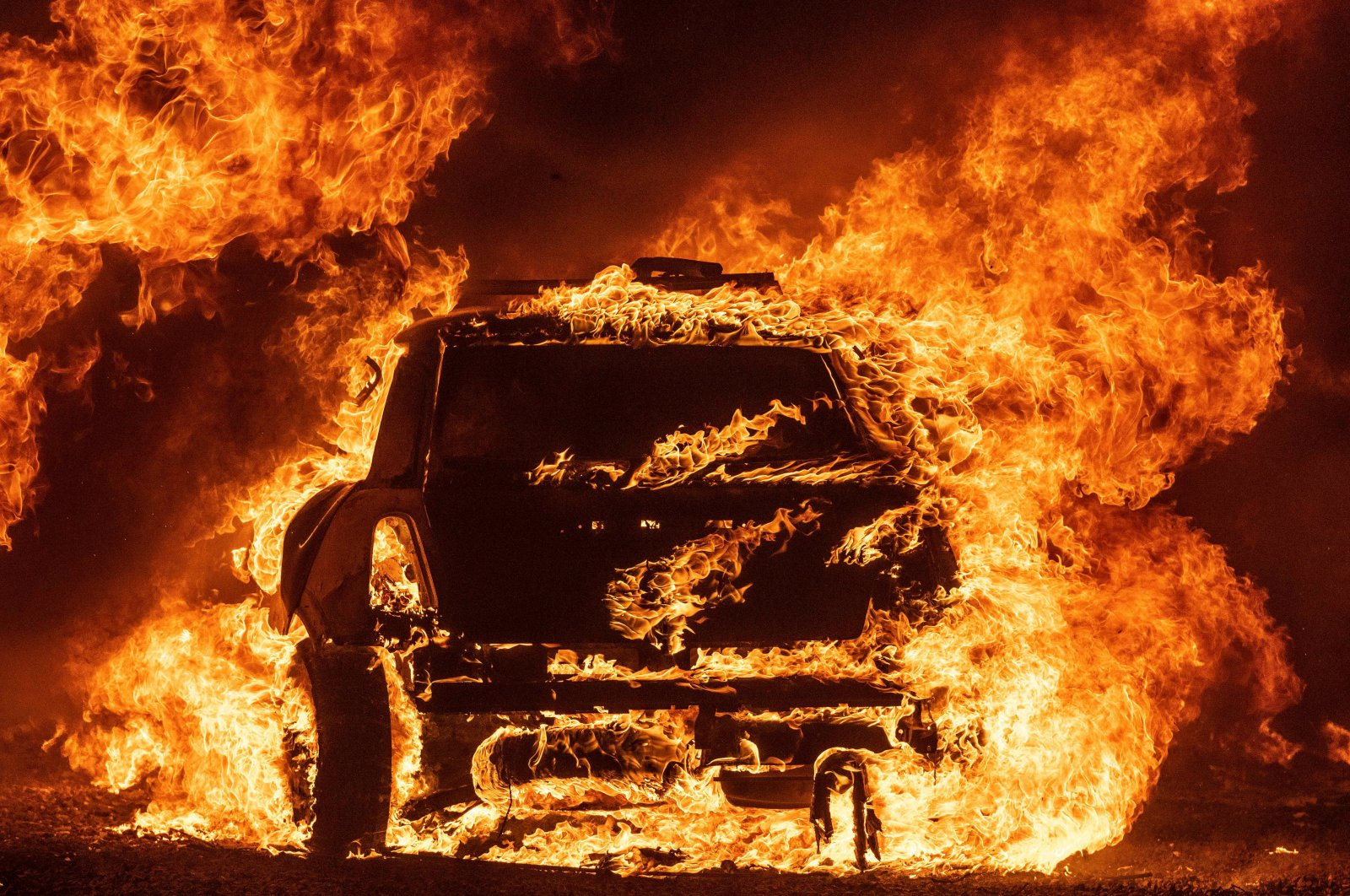 A car burns while parked at a residence during the LNU Lightning Complex fire in Vacaville, California on Aug. 19, 2020. (AFP Photo)