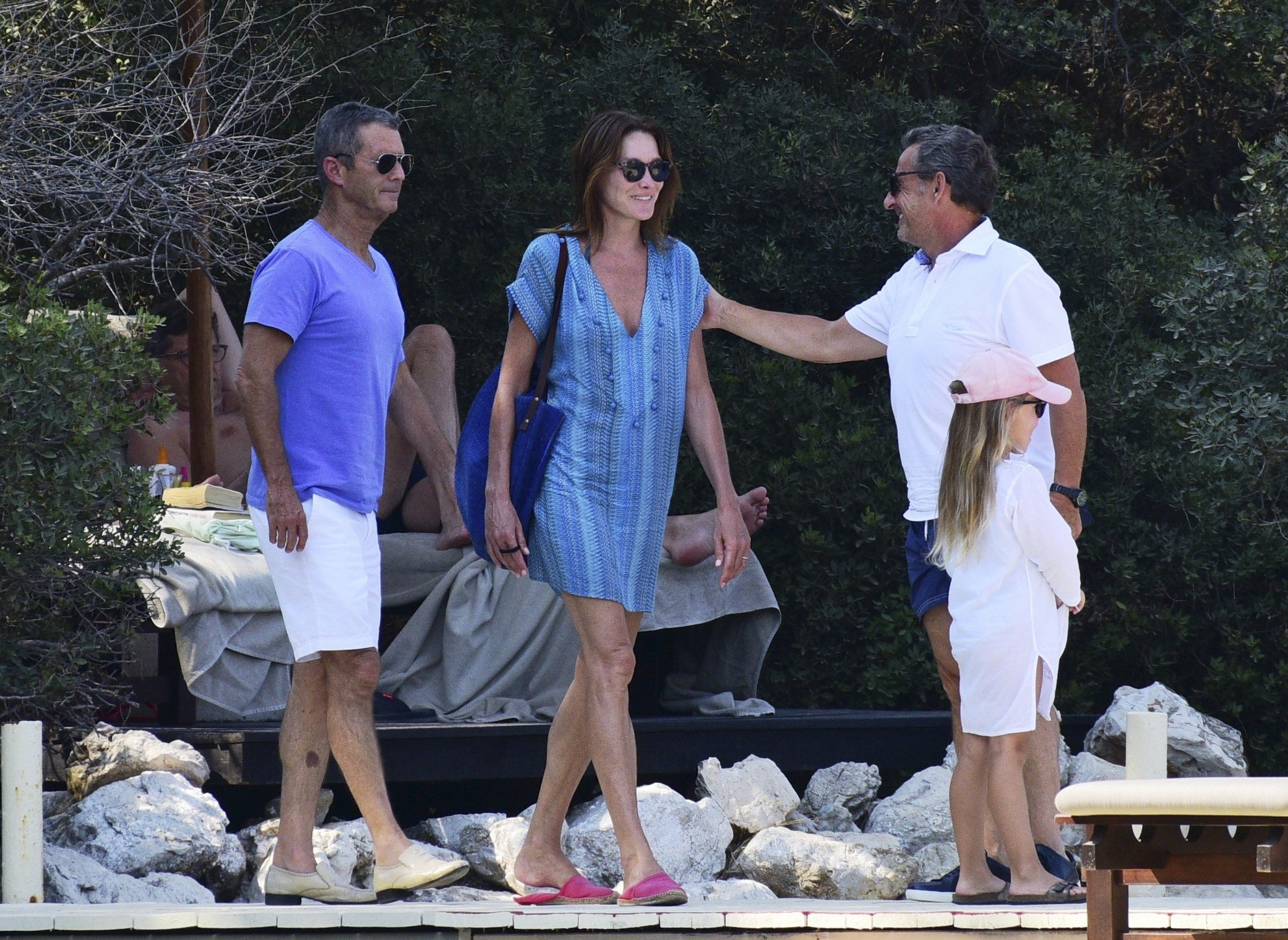 France's former President Nikolas Sarkozy, right, accompanied by his wife Carla Bruni-Sarkozy, centre, and other members of their family and friends enjoy their holidays near the coastal city of Bodrum, western Turkey Monday, Aug. 20, 2018. (AP Photo)