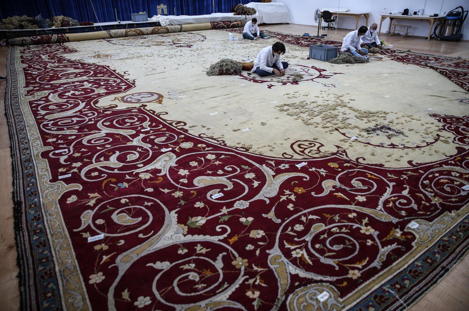 Restoration experts work on the carpet, Istanbul, Turkey, Aug. 19, 2020. (AA Photo)