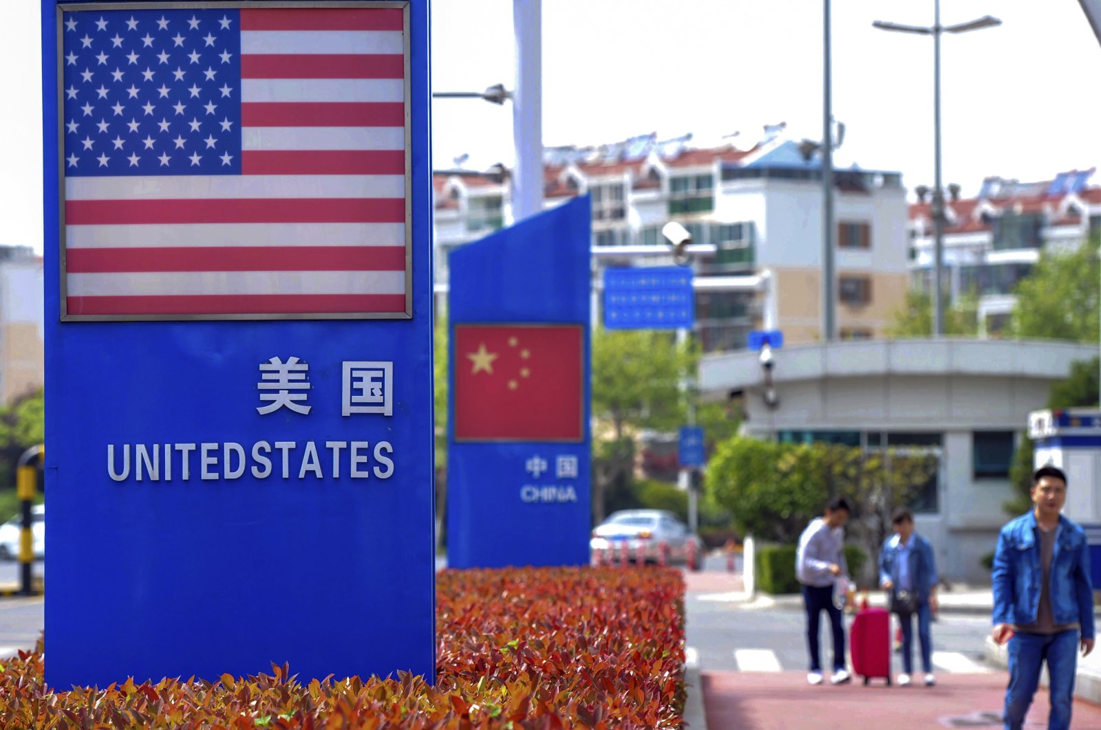 People walk by display boards featuring the U.S. and Chinese flags in a special trade zone in Qingdao in eastern China's Shandong province, May 8, 2019. (AP Photo)