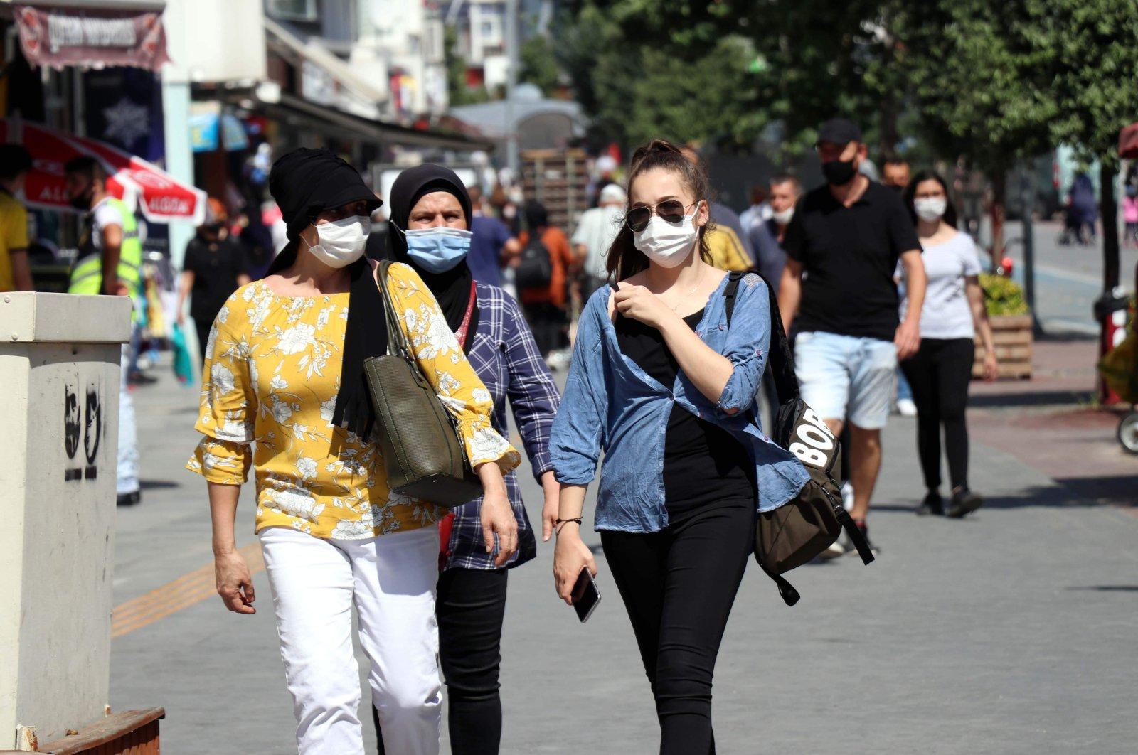 People wearing protective masks against the coronavirus walk on a street in Bolu, northern Turkey, Aug. 20, 2020. (DHA Photo)