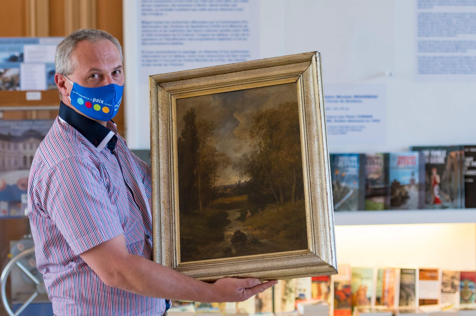 Philippe Hansch, director of the World Peace Center, presents the painting by the French painter Nicolas Rousseau in Verdun, France on Aug. 17, 2020. (AFP Photo)