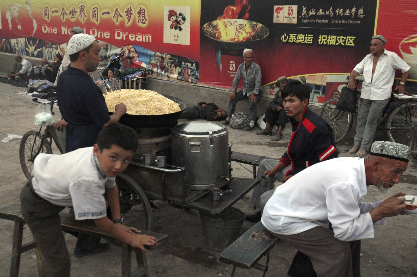 Uighurs rest near a food stall and Beijing Olympic Games billboards in Kashgar in western Xinjiang province, China, Aug. 6, 2008. (AP Photo)