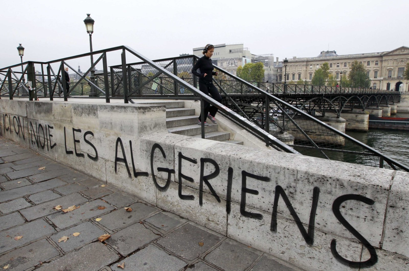 """A slogan """"We drown Algerians here"""" is painted on the wall of the Seine river banks near the Pont des Arts in Paris October 17, 2011 to mark the 50th anniversary of the Paris massacre of 1961. (Reuters Photo)"""