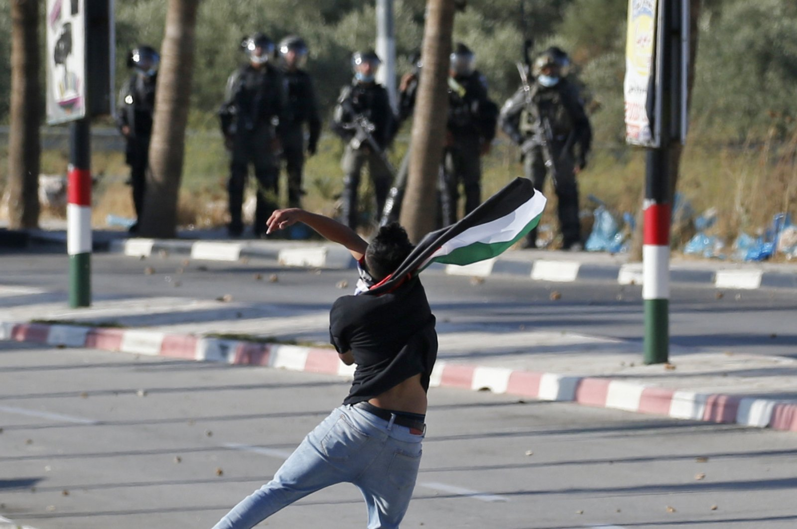 A Palestinian protester hurls stones at Israeli security forces amid clashes following a demonstration against the United Arab Emirates' decision to normalize ties with Israel, in the village of Turmus Aya near the occupied West Bank city of Ramallah, August 19, 2020. (AFP Photo)