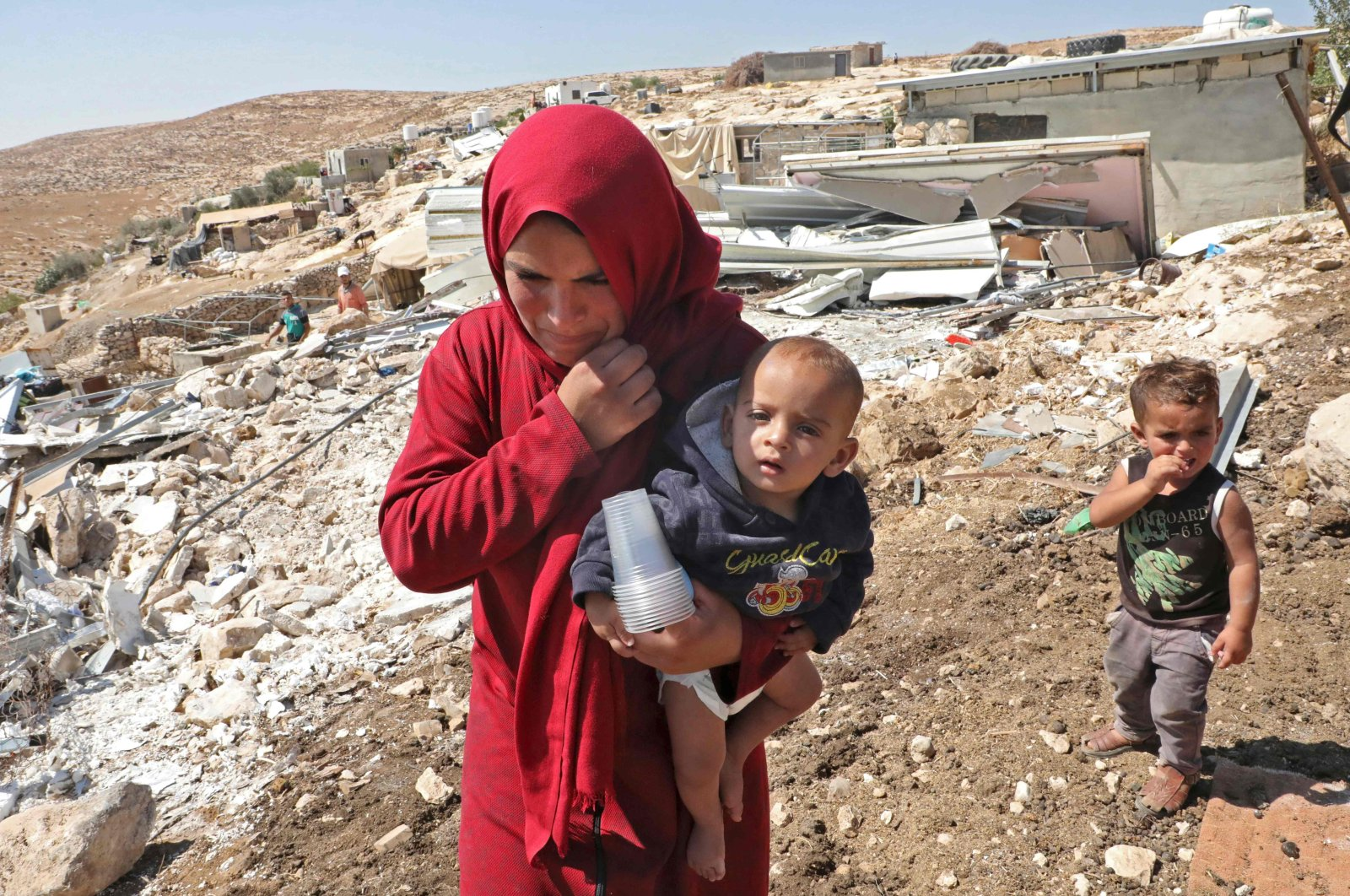 A Palestinian woman walks carrying a baby past wreckage of mobile homes built with European Union funding and destroyed by Israeli forces in the village of Mufagara south of Yatta near Hebron, as they were purportedly built without Israeli authorization, occupied West Bank, Sept. 11, 2019. (AFP Photo)