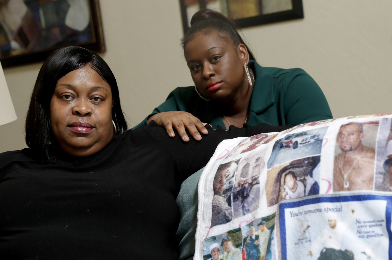 In this June 5, 2020, file photo, Mussallina Muhaymin, left, and Zarinah Tavares, sisters of Muhammad Abdul Muhaymin Jr., a homeless man who died while in Phoenix police custody, pose in Phoenix. (AP Photo)