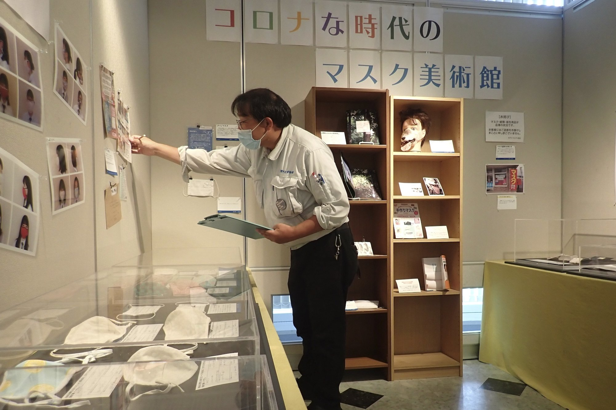 Curator Makoto Mochida examines newspaper clips and other items he has collected to document how life was affected by the coronavirus pandemic, at the Historical Museum of Urahoro in Urahoro, Hokkaido island, northern Japan, Aug. 16, 2020. (AP PHOTO)