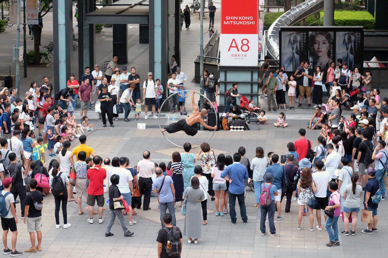 Taiwanese American street artist Isaac Hou (C) perform with a cyr wheel in Taipei, Taiwan, Aug. 12, 2018  (AFP Photo)
