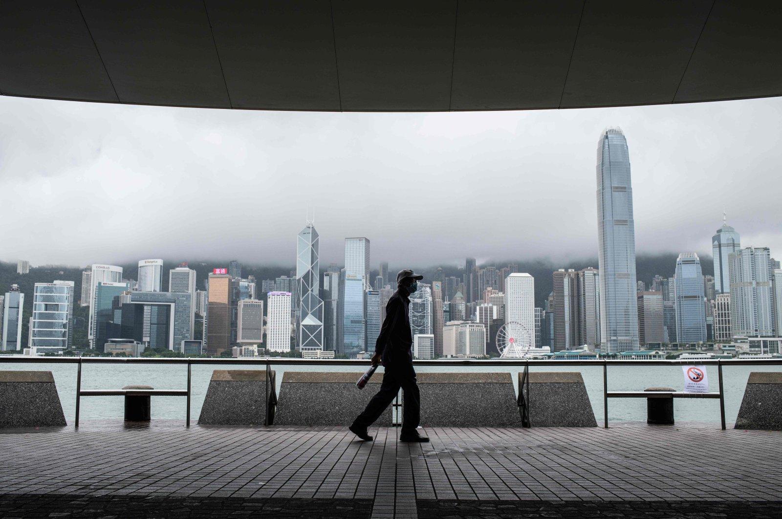 A man walks on Kowloon's Tsim Sha Tsui waterfront facing Victoria Harbor and the Hong Kong skyline (back), Hong Kong, Aug. 19, 2020. (AFP Photo)