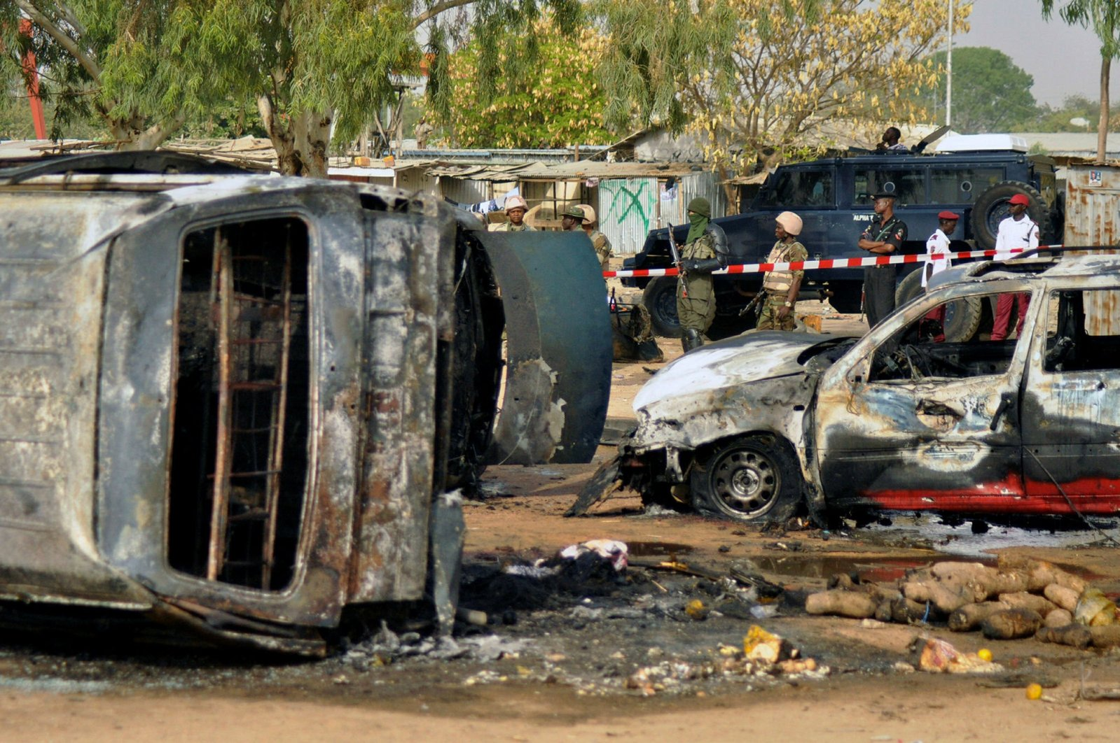 In this file photo, police officers stand guard following a suicide bomb explosion at a bus station in Kano, Nigeria, Feb. 24, 2015. (AP Photo)