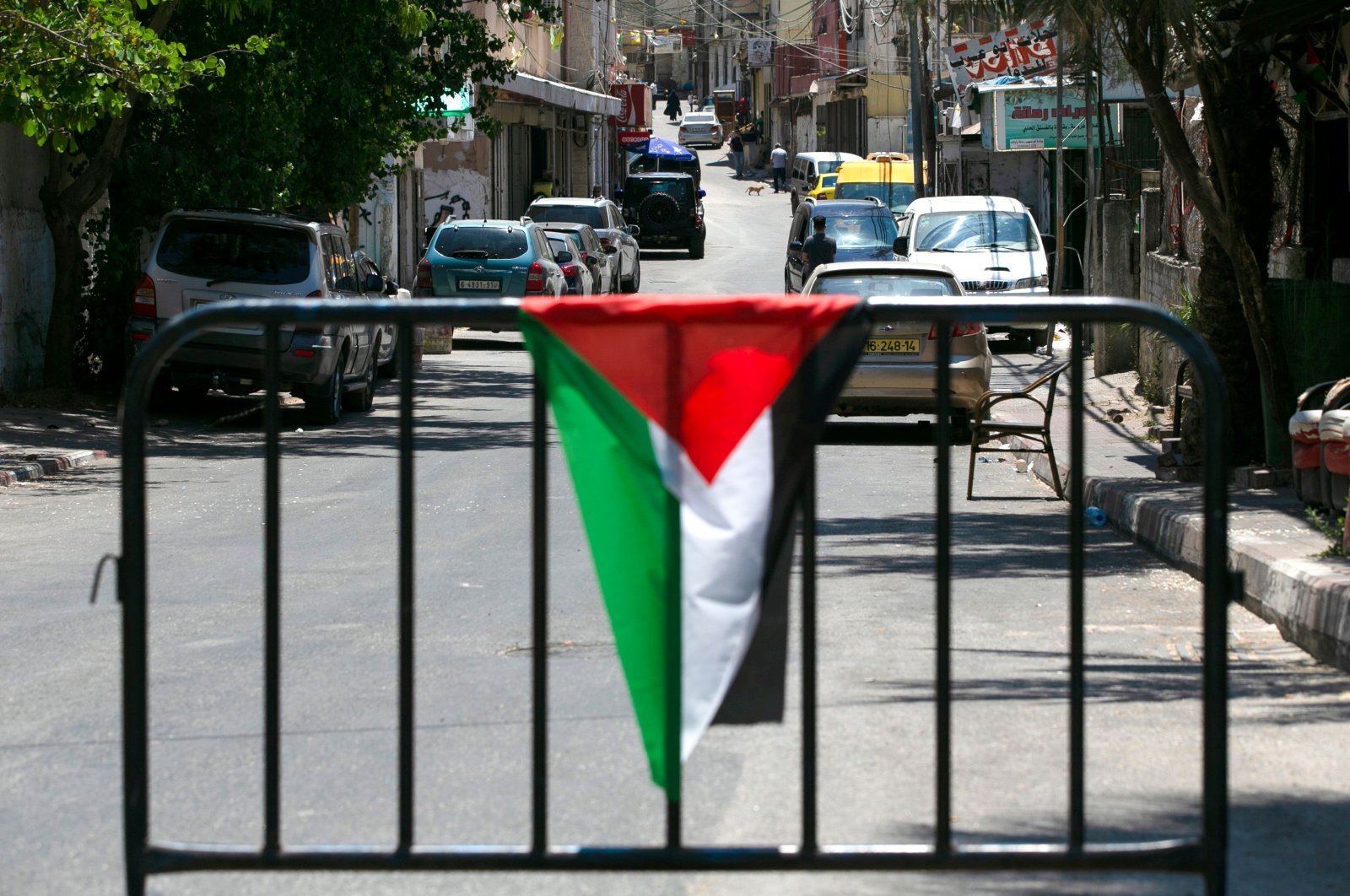 A Palestinian flag is draped over a metal barrier at a checkpoint at the entrance of Amari refugee camp near Ramallah, occupied West Bank, July 24, 2020. (AFP Photo)