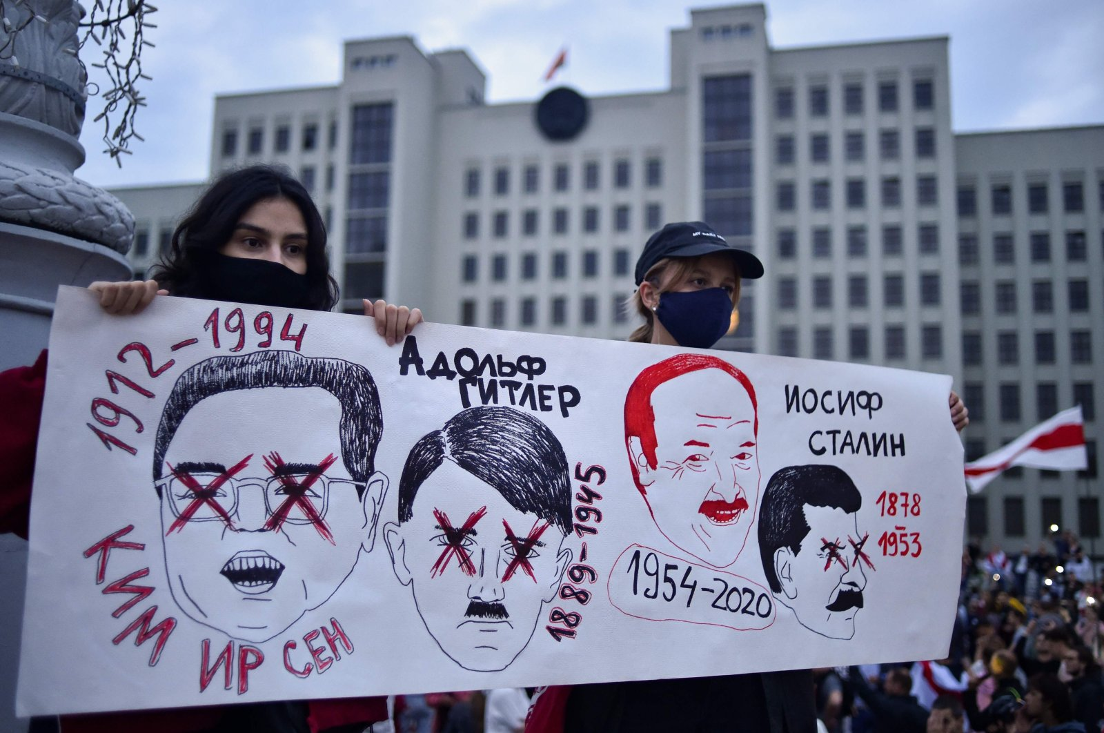 Women hold a placard with drawings of Kim Il Sung, Adolf Hitler, Alexander Lukashenko and Joseph Stalin during a rally to protest disputed presidential election results on Independence Square, Minsk, Belarus, Aug. 20, 2020. (AFP Photo)