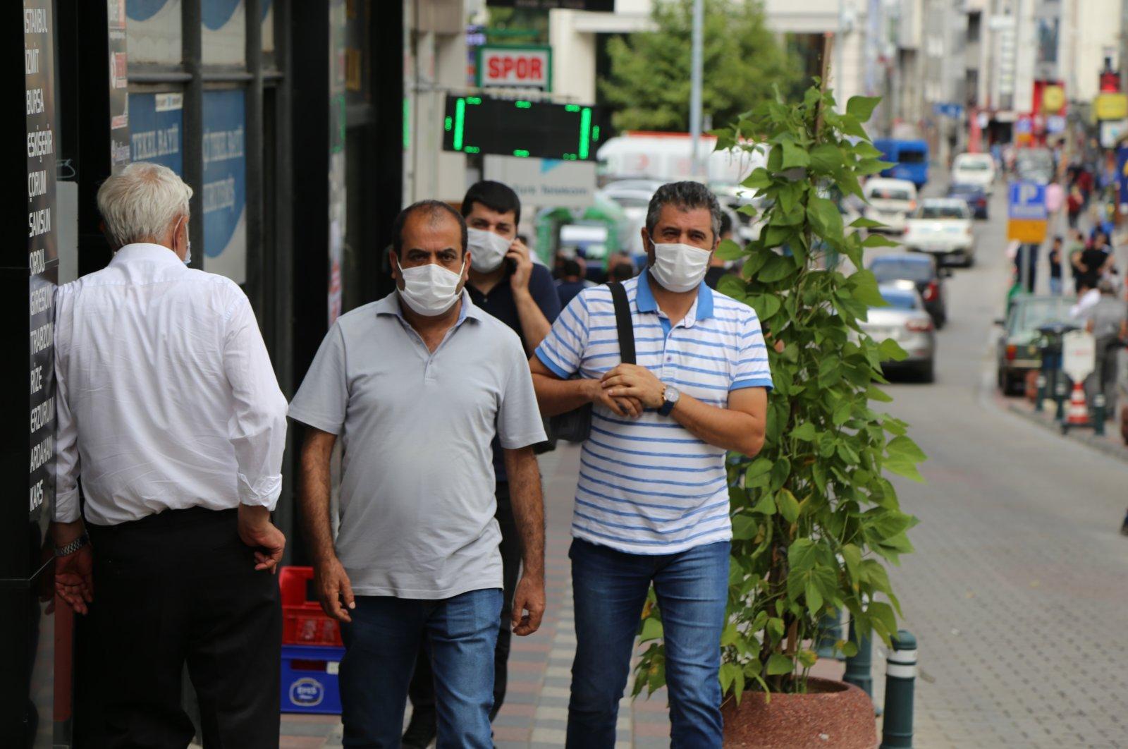 People wearing protective masks walk on a street in Artvin, northeastern Turkey, Aug. 19, 2020. (IHA Photo)