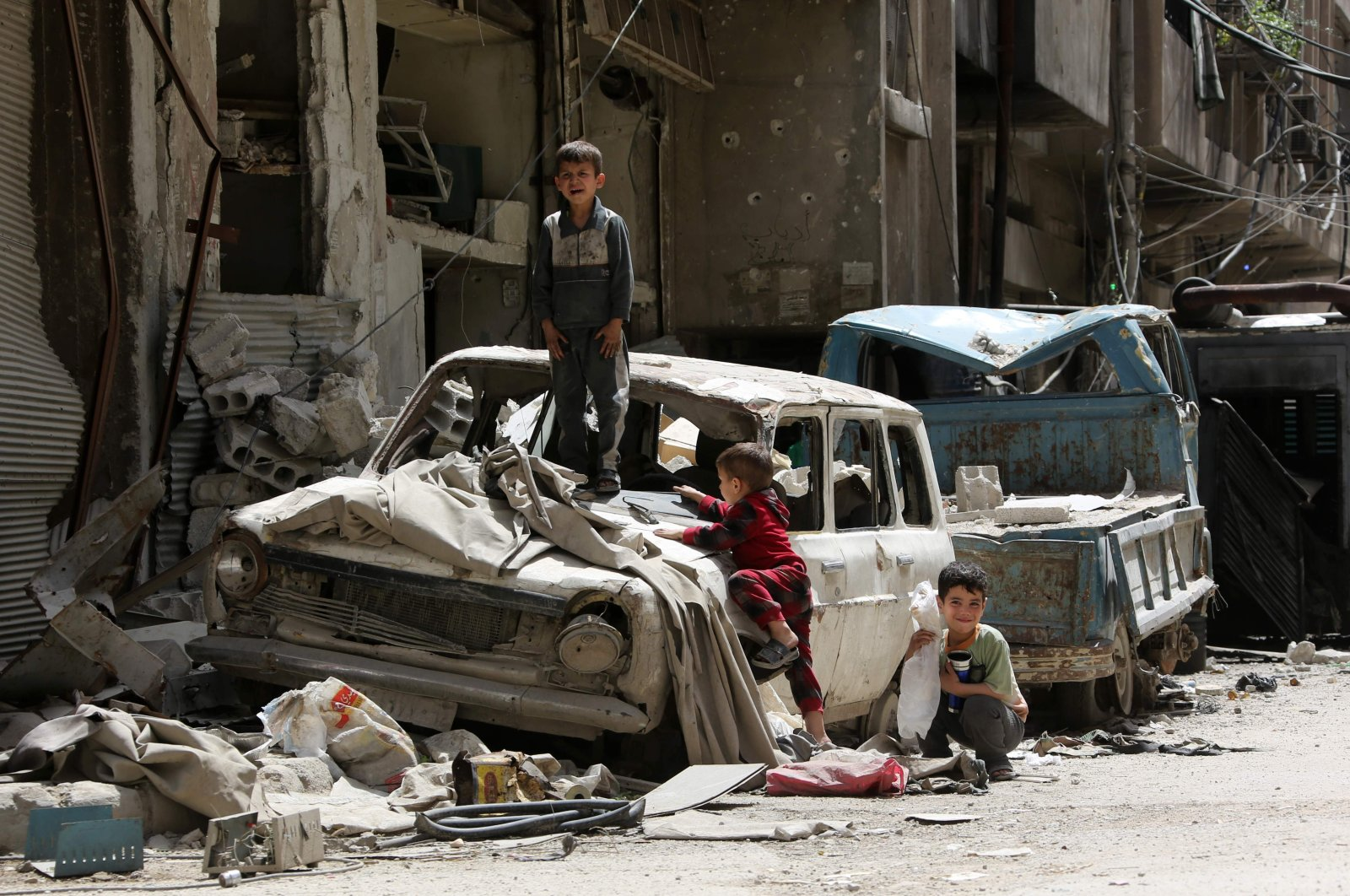 Syrian boys play on a destroyed car in the former opposition-held Syrian town of Douma on the outskirts of Damascus, April 19, 2018. (AFP)