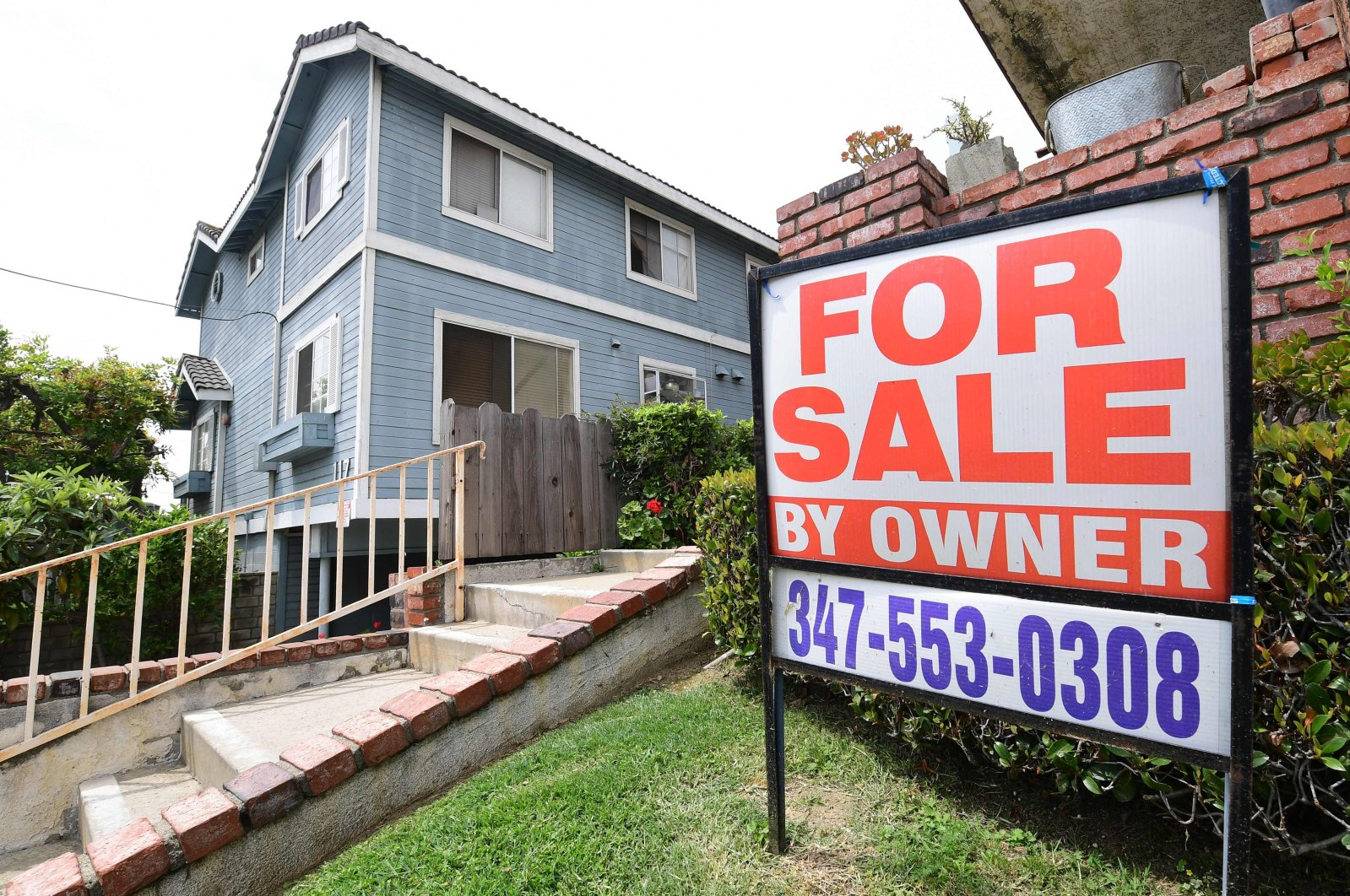 "A ""For Sale by Owner"" sign is posted in front of a property in Monterey Park, California, U.S., April 29, 2020. (AFP Photo)"