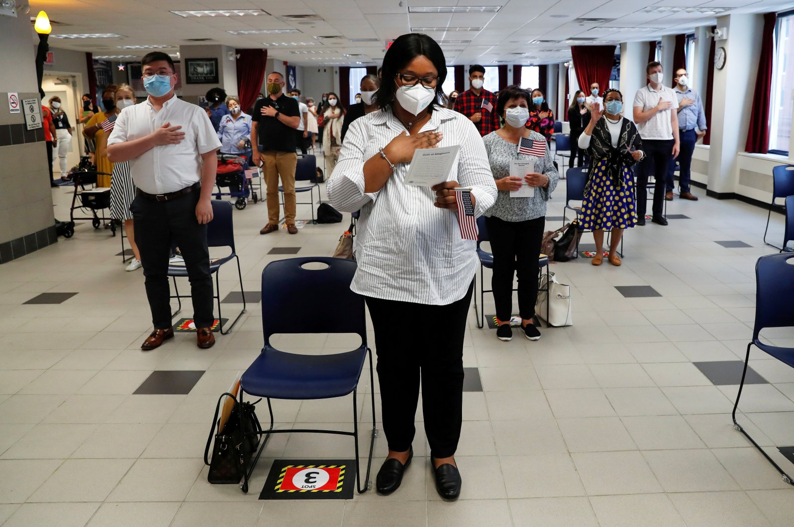 Ifeoma Eh, a citizen candidate from Nigeria, stands with others socially distanced and wearing protective face masks, as the outbreak of the coronavirus disease (COVID-19) continues, during a U.S. Citizenship and Immigration Services (USCIS) naturalization ceremony in New York, U.S., July 22, 2020. (Reuters Photo)