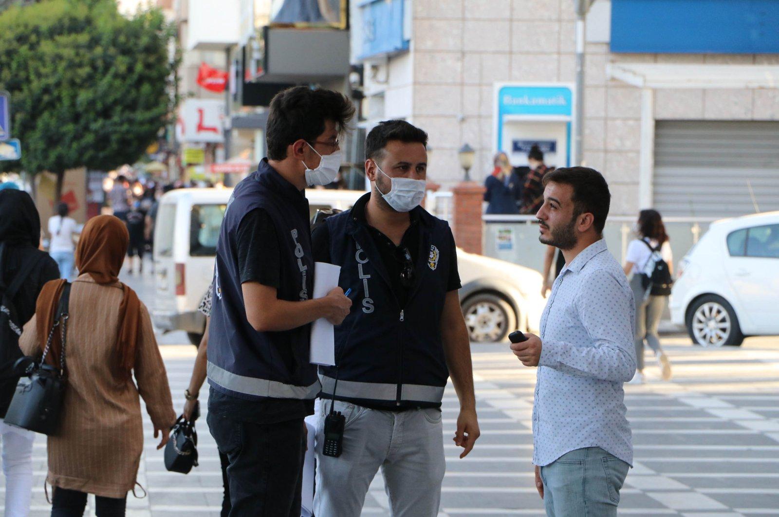 Policemen in southeastern Şanlıurfa province warn a citizen to wear a mask on July 24, 2020 (AA Photo)