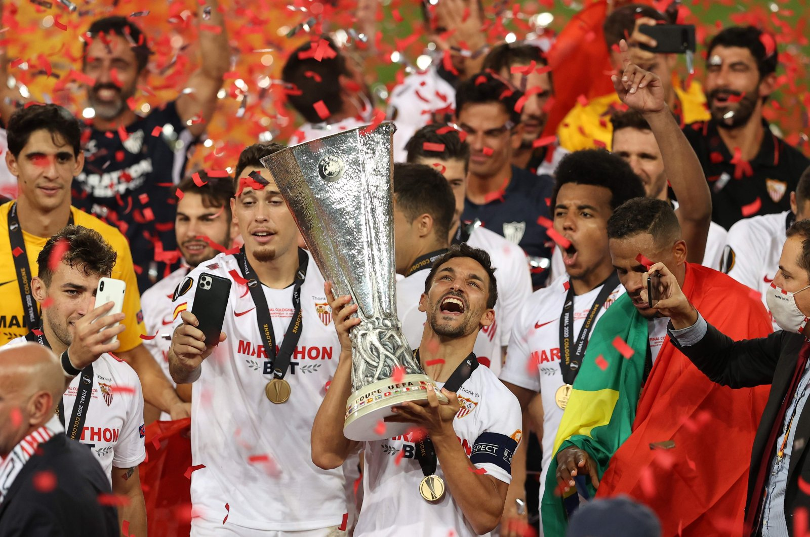 Sevilla's Spanish midfielder Jesus Navas holds the trophy as Sevilla's players celebrate  after winning the UEFA Europa League final football match Sevilla v Inter Milan on August 21, 2020, in Cologne, western Germany. (AFP Photo)