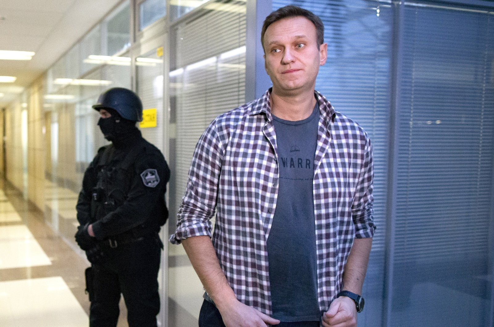 In this Dec. 26, 2019, file photo, Russian opposition leader Alexei Navalny speaks to the media in front of a security officer standing guard at the Foundation for Fighting Corruption office in Moscow, Russia. (AP Photo)