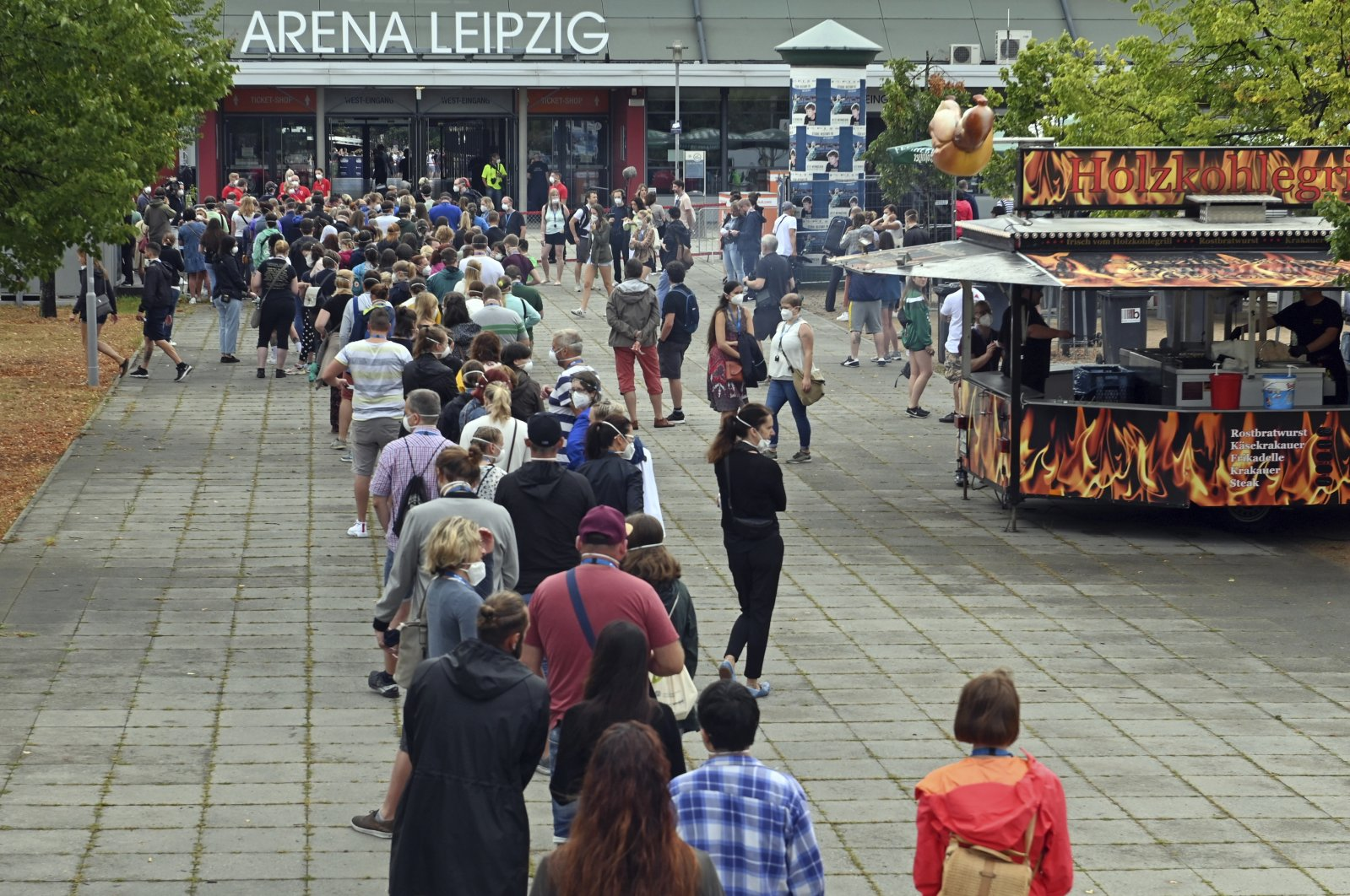 Test persons of a large-scale experiment of the University Medicine Halle/Saale are standing at the entrance in front of the Arena Leipzig, Saxony, Leipzig on Aug. 22, 2020. (AP Photo)