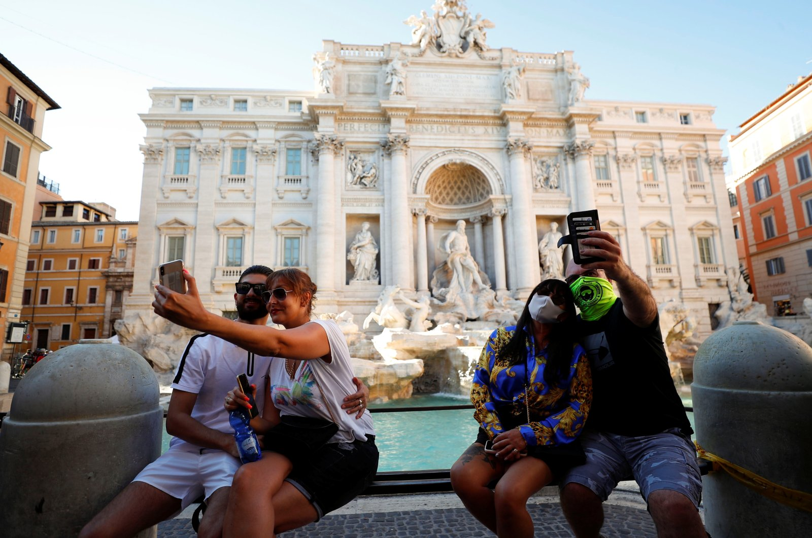 A couple wears face masks while other couple does not as they both take selfies in front of Rome's Trevi Fountain following a government decree that states face coverings must be worn between 6 p.m. and 6 a.m. in areas where gatherings are common, Aug. 19, 2020. (REUTERS Photo)