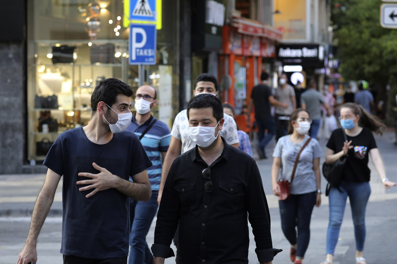 People wearing face masks to protect against the spread of coronavirus, walk in Ankara, Turkey, Thursday, Aug. 6, 2020. Turkey's interior ministry announced new measures Wednesday to curb the spread of COVID-19 as daily confirmed cases peaked above 1,000. (AP Photo)