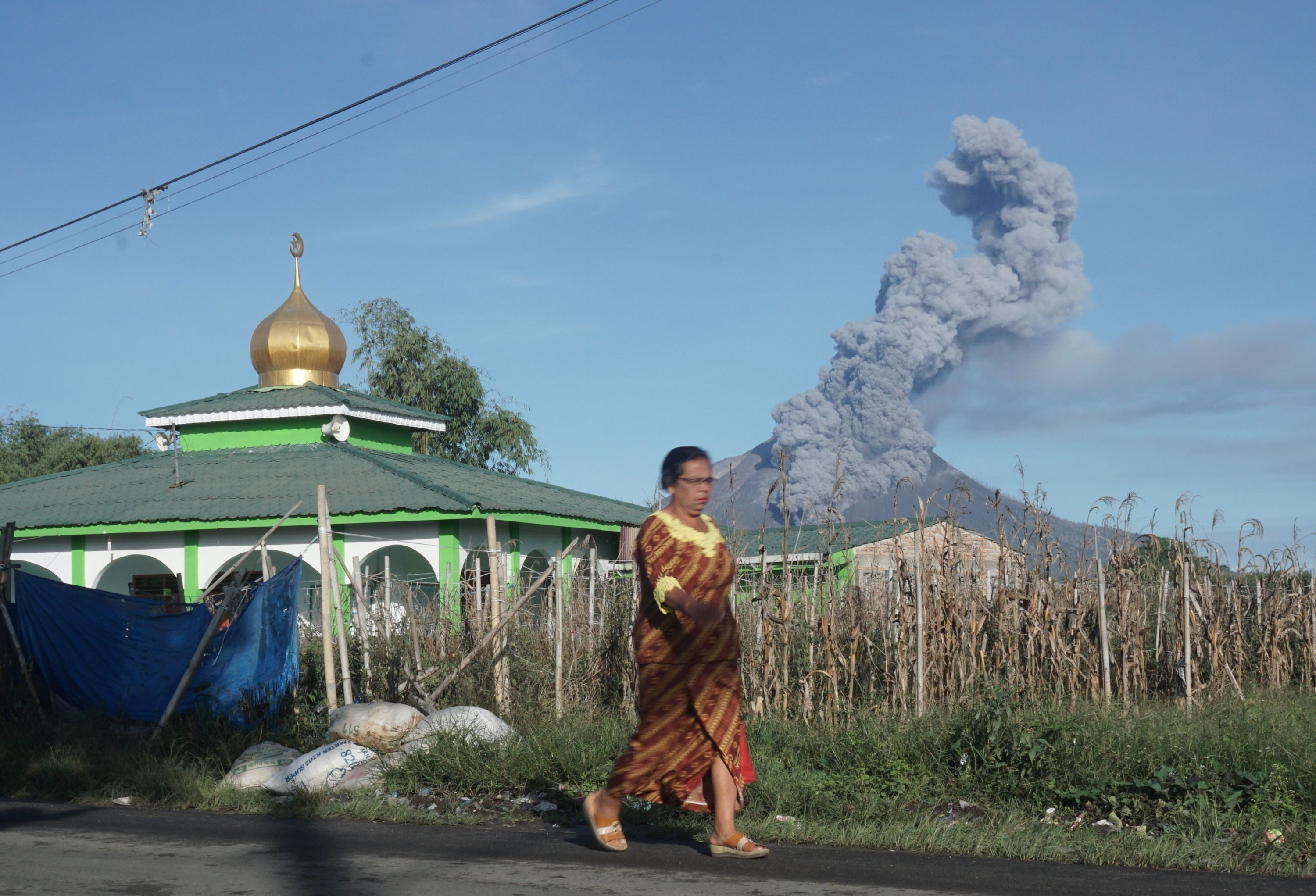 A woman walks as Mount Sinabung spews thick smoke into the air in Karo, North Sumatra, Indonesia, Aug. 23, 2020. (AFP Photo)