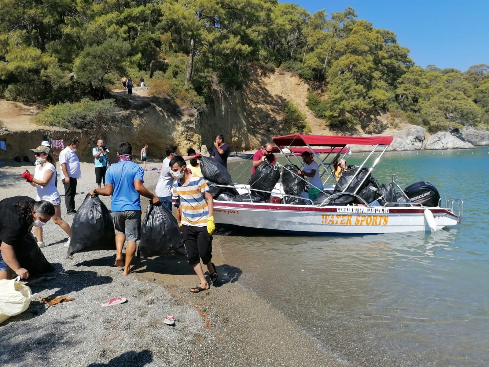 Volunteers load plastic bags of garbage onto a boat in Darboğaz Bay, in the Fethiye district of Muğla province, southwestern Turkey, Aug. 23, 2020. (AA Photo)
